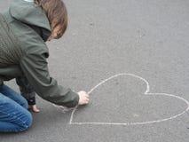 Pojken drar hjärta med krita på jordningen royaltyfri foto