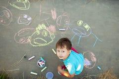 Pojken drar med krita på trottoaren royaltyfri foto
