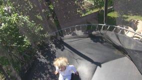 Pojken för blont hår hoppar på trampolinen Tre år gammalt barn har gyckel l?ngsam r?relse arkivfilmer