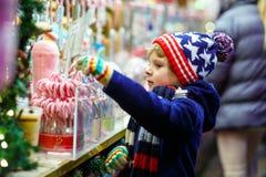 Pojken för den lilla ungen med ställningen för godisrottingen på jul marknadsför Arkivfoto