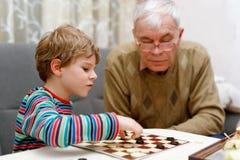 Pojken för den lilla ungen och pensionärfarfadern som tillsammans spelar kontrollörer, spelar royaltyfria foton