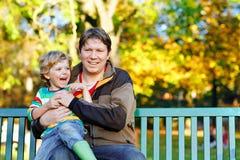 Pojken för den lilla ungen och den unga fadern som tillsammans sitter i färgrika kläder på bänk parkerar in Gulligt sunt barn och royaltyfri foto