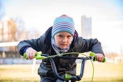Pojken för det lilla barnet på cykeln parkerar in utomhus- Ett barn rider barns cykel royaltyfri fotografi