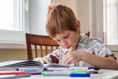 Pojken förbereder sig för skola - lär att skriva brev och diagram royaltyfri foto