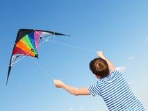 Pojken flyger draken in i blå himmel Royaltyfri Bild