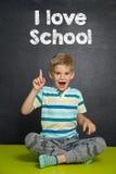 Pojken framme av skolförvaltningen med text ÄLSKAR JAG SKOLAN Arkivbilder
