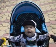 Pojken gäspar i den blåa stolleren Fotografering för Bildbyråer