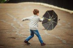 Pojken går med ett paraply Arkivbilder