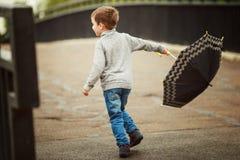 Pojken går med ett paraply Royaltyfria Bilder