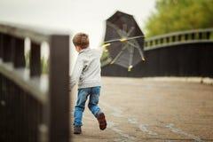Pojken går med ett paraply Arkivfoto