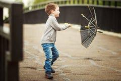 Pojken går med ett paraply Royaltyfri Bild