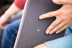 Pojken gör bulthål på griptapen på en skateboard Royaltyfria Bilder