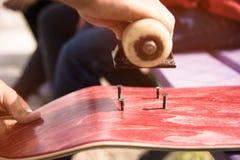 Pojken gör bulthål på griptapen på en skateboard Arkivbild