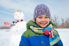 Pojken gör en snögubbe Royaltyfri Fotografi