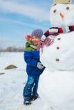 Pojken gör en snögubbe Arkivfoton
