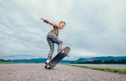 Pojken gör ett trick med skateboarden royaltyfri bild