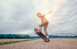 Pojken gör ett trick med skateboarden fotografering för bildbyråer