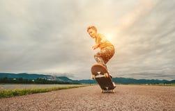 Pojken gör ett trick med skateboarden arkivbild