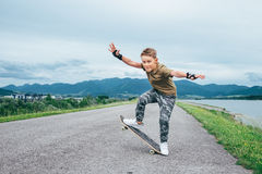 Pojken gör ett trick på skateboarden arkivbilder