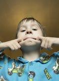 Pojken gör grimasen på hans framsida Pojkeapan och gör den konstiga framsidan pojke Royaltyfri Fotografi