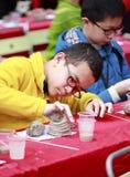 Pojken gör krukmakeri försiktigt Royaltyfri Bild