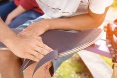 Pojken gör ren den klippte kanten griptapen på en skateboard Arkivbild