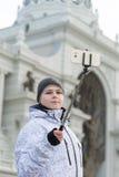 Pojken gör selfie på telefonen med selfie att klibba på bakgrund av sikt Arkivfoton