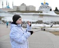 Pojken gör selfie på telefonen med självhäftande mot bakgrunden av den Kazan Kreml, Ryssland Royaltyfria Bilder