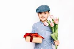 Pojken ger blommor och en gåva Arkivbild