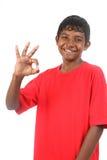 pojken ger den le tonåringen för den ok röda skjortasignaleringen royaltyfri bild