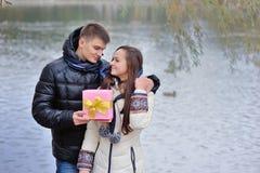 Pojken ger en flicka en gåva Arkivbild