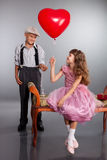 Pojken ger en röd ballong till flickan Royaltyfri Fotografi