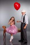 Pojken ger en röd ballong till flickan Arkivbild