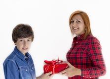 Pojken ger julgåvan till hans moder Arkivbilder