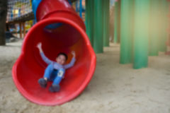 Pojken glider ner en spiral glidbana Arkivfoton