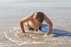 Pojken gör push-UPS på stranden Royaltyfri Fotografi