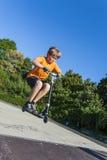 Pojken har den roliga ridningpushsparkcykeln på skridskon att parkera Royaltyfria Bilder