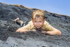 Pojken har gyckel i dyerna av stranden i havet royaltyfria foton