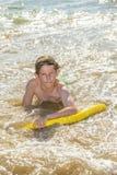 Pojken har gyckel i havet med hans boogiebräde Fotografering för Bildbyråer