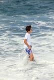 Pojken har gyckel i spumen på den svarta stranden royaltyfri foto