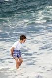 Pojken har gyckel i spumen på den svarta stranden royaltyfri fotografi