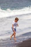 Pojken har gyckel i spumen på den svarta stranden Royaltyfria Foton