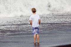 Pojken har gyckel i spumen på den svarta vulkaniska stranden royaltyfria bilder