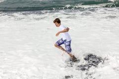 Pojken har gyckel i spumen på den svarta vulkaniska stranden arkivbilder