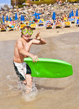Pojken har gyckel med surfingbrädan Royaltyfri Foto