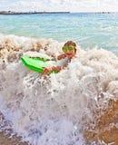 Pojken har gyckel med surfingbrädan Fotografering för Bildbyråer