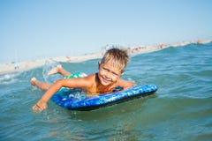 Pojken har gyckel med surfingbrädan Arkivbilder