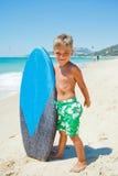 Pojken har gyckel med surfingbrädan Royaltyfria Foton