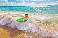 Pojken har gyckel med surfingbrädan Royaltyfria Bilder