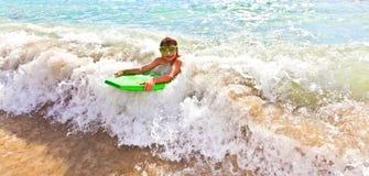 Pojken har gyckel med surfingbrädan Royaltyfri Fotografi